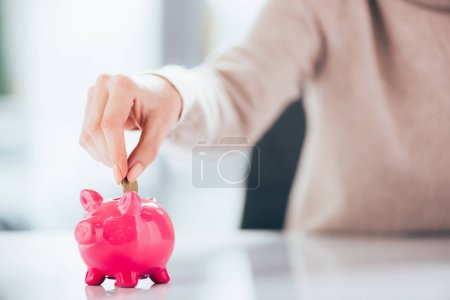 close-up partial view of woman putting coin into pink piggy bank