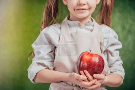 cropped view of child holding apple on blurred background, earth day concept