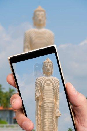 Buddha statue on smartphone screen. Buddha image made of white stone.