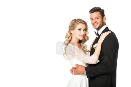 smiling newlyweds embracing and looking at camera isolated on white