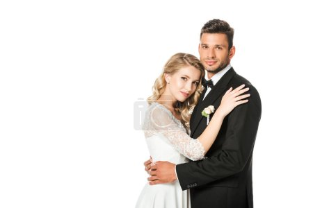 young newlyweds embracing and looking at camera isolated on white