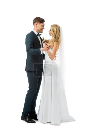 happy bride in white wedding dress dancing with smiling groom in black elegant suit isolated on white