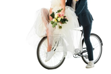 partial view of bride with wedding bouquet sitting on bicycle together with groom isolated on white