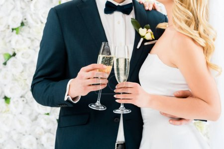 cropped view of groom and bride holding glasses of champagne on white floral background