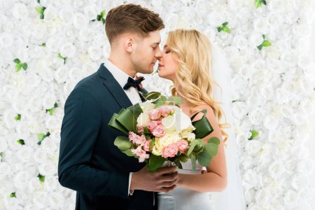 happy young bride and groom kissing while holding wedding bouquet on white floral background