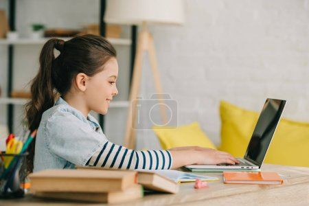 side view of adorable child using laptop while sitting at desk with books and doing homework