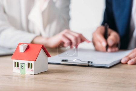 cropped shot of businesswoman and client signing loan agreement near house model on table