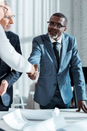 selective focus of businessman in glasses looking at african american man shaking hands with woman in office
