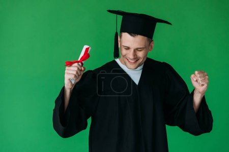 smiling student in academic cap holding diploma with red ribbon and showing yes gesture isolated on green