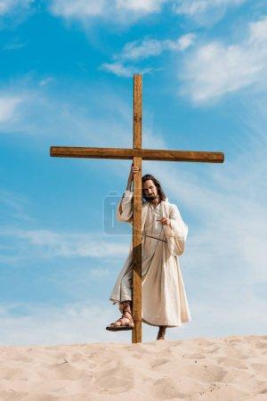 bearded man standing with wooden cross in desert