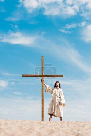 bearded man standing with wooden cross in desert on sand