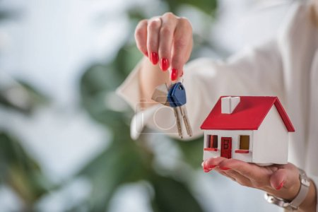 partial view of businesswoman showing house model and keys