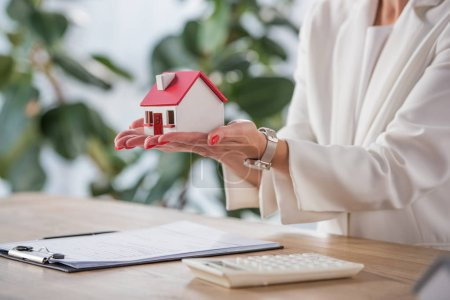 partial view of businesswoman holding house model near clipboard and calculator