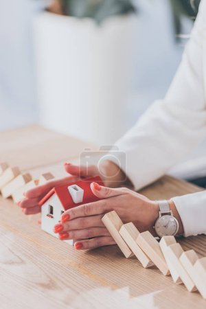 partial view of businesswoman protecting house model from falling wooden blocks with hands