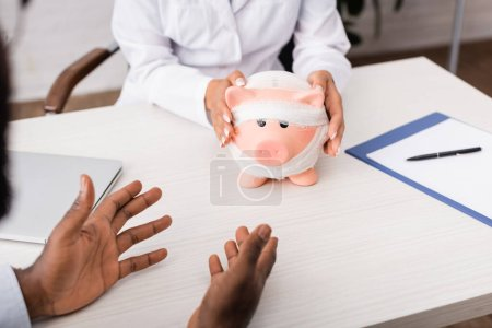 cropped view of african american patient gesturing with hands near doctor touching piggy bank, wrapped in bandage, medical insurance concept