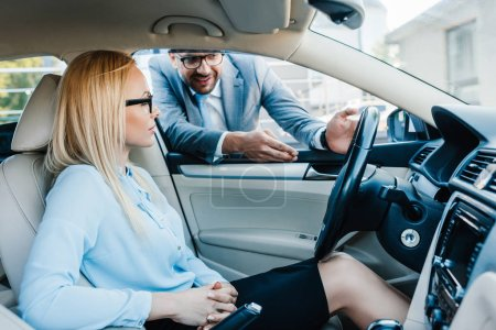 businessman giving advice to businesswoman in car