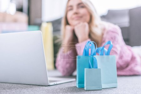selective focus of shopping bags with dreamy woman on background