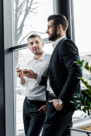 businessmen standing with hands in pockets and holding glasses with alcohol drinks
