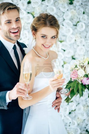 attractive bride and handsome bridegroom smiling and holding champagne glasses