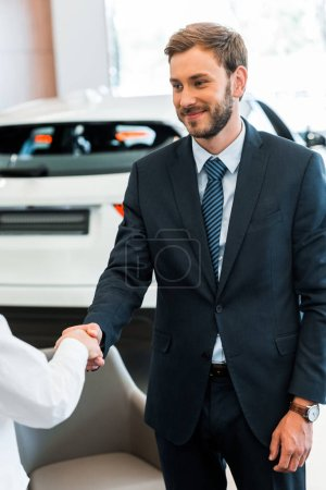 cropped view of woman shaking hands with happy car dealer in car showroom