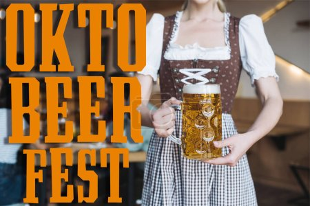 partial view of waitress in german national costume holding mug of light beer near Oktobeerfest illustration
