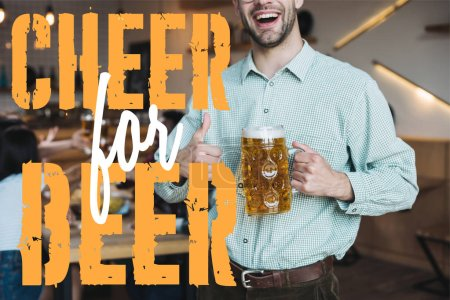 cropped view of smiling young man holding mug of lager beer and showing thumb up near cheer for the beer illustration