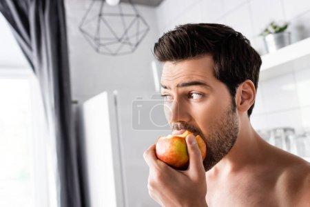 surprised shirtless man eating apple on kitchen