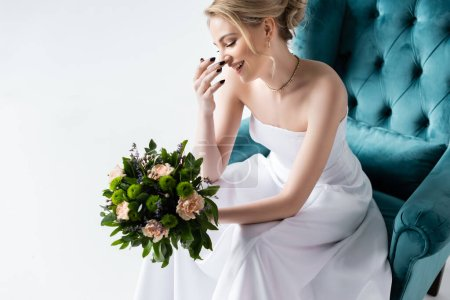 smiling bride in elegant wedding dress holding flowers while sitting in armchair and touching face isolated on white