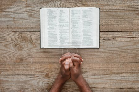 cropped shot of african american man praying with holy bible on rustic wooden table