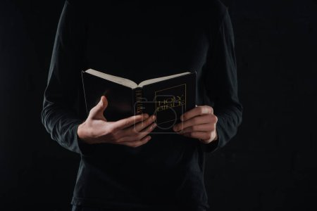 cropped shot of priest reading holy bible isolated on black