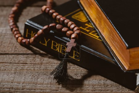 close-up shot of holy bibles with beads on wooden table
