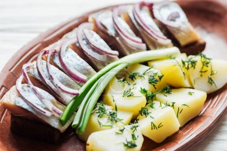 close up of delicious marinated herring with potatoes and onions in earthenware plate