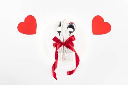 elevated view of plate with cutlery wrapped by festive ribbon bow near heart symbols isolated on white, st valentine day concept