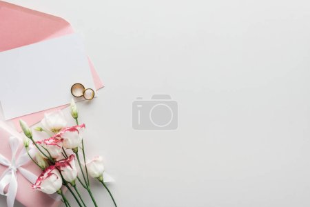 top view of empty card with pink envelope, flowers, wrapped gift and golden wedding rings on grey background