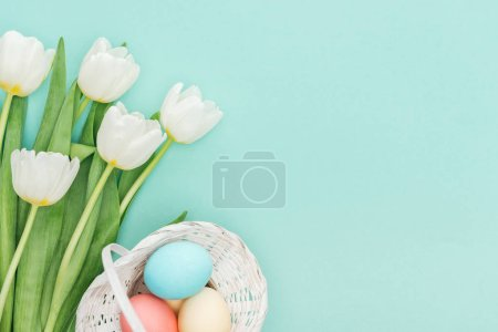 top view of tulip flowers and easter eggs in wicker basket isolated on blue with copy space