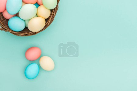 top view of traditional pastel easter eggs in wicker basket isolated on blue with copy space