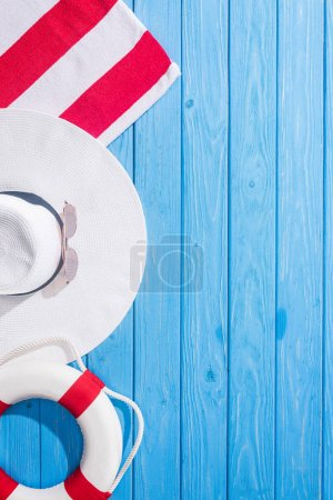 top view of striped towel, white sunglasses, lifebuoy, floppy hat on blue wooden background with copy space