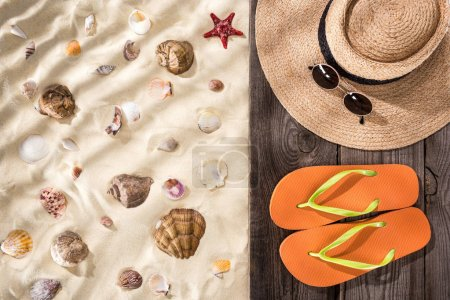 Top view of seashells and starfish on sand with orange flip flops, straw hat and sunglasses on wooden brown board