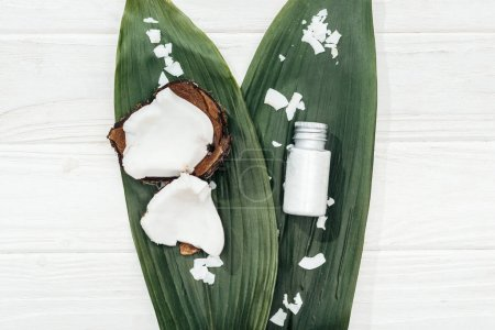 top view of green palm leaves with coconut flakes and coconut lotion on wooden surface