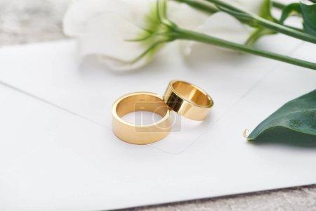 golden wedding rings on white envelope near white flowers