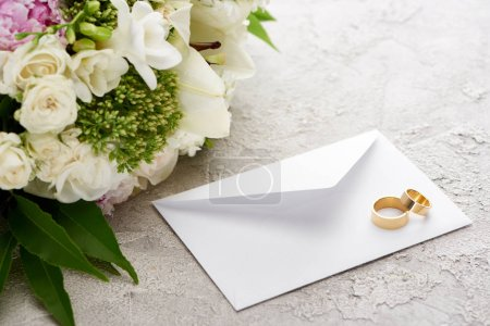 wedding rings on white envelope near bouquet of flowers on textured surface
