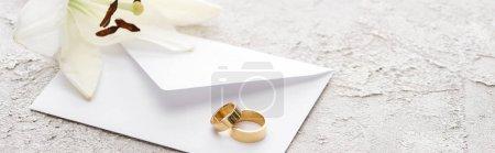 panoramic shot of golden wedding rings on white envelope near lily flower