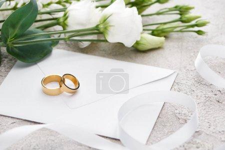 golden wedding rings on white envelope near eustoma flowers and white ribbon