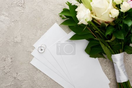 top view of silver rings on invitation cards near bouquet on textured surface