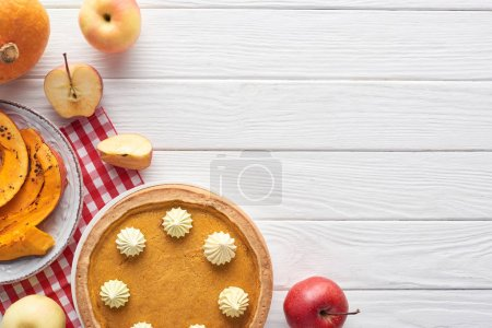 tasty pumpkin pie with whipped cream on checkered napkin near baked and raw pumpkins, whole and cut apples on white wooden table