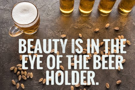 top view of bottles and glass of light beer near scattered pistachios on grey surface with beauty is in the eye of the beer holder illustration