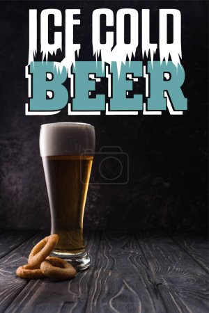 glass of fresh light beer near fried onion rings on wooden table with ice cold beer lettering
