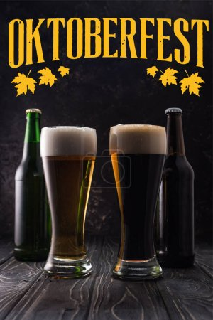 glasses of fresh light and dark beer near bottles on wooden table with yellow Oktoberfest lettering