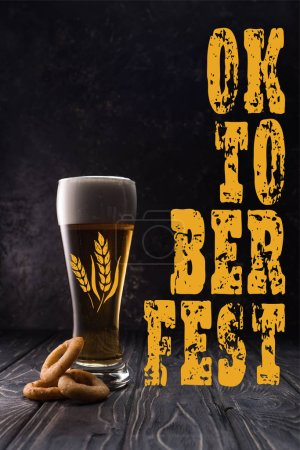 glass of fresh light beer near fried onion rings on wooden table with yellow oktobeer fest lettering