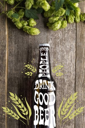 top view of fresh beer in bottle with good people drink good beer lettering near green hop on wooden surface